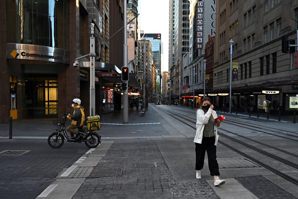 A woman crosses the street as a delivery rider drives past in the Sydney CBD, Australia.