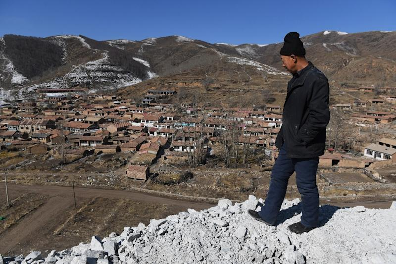 Rsident Ying Gui looks over a village that is to be demolished to make way for the 2002 Winter Games