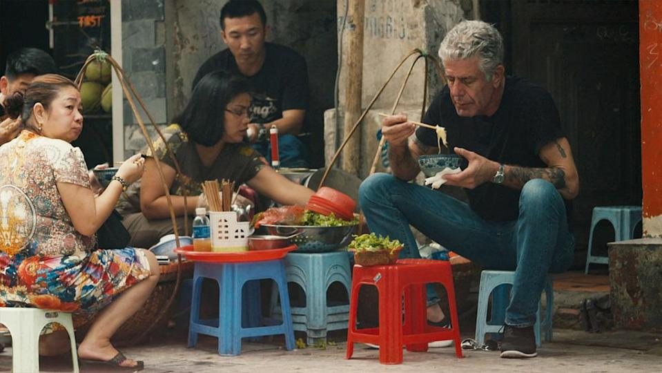Bourdain about to eat a bowl of noodles, sitting on a small chair in a city street in Asia