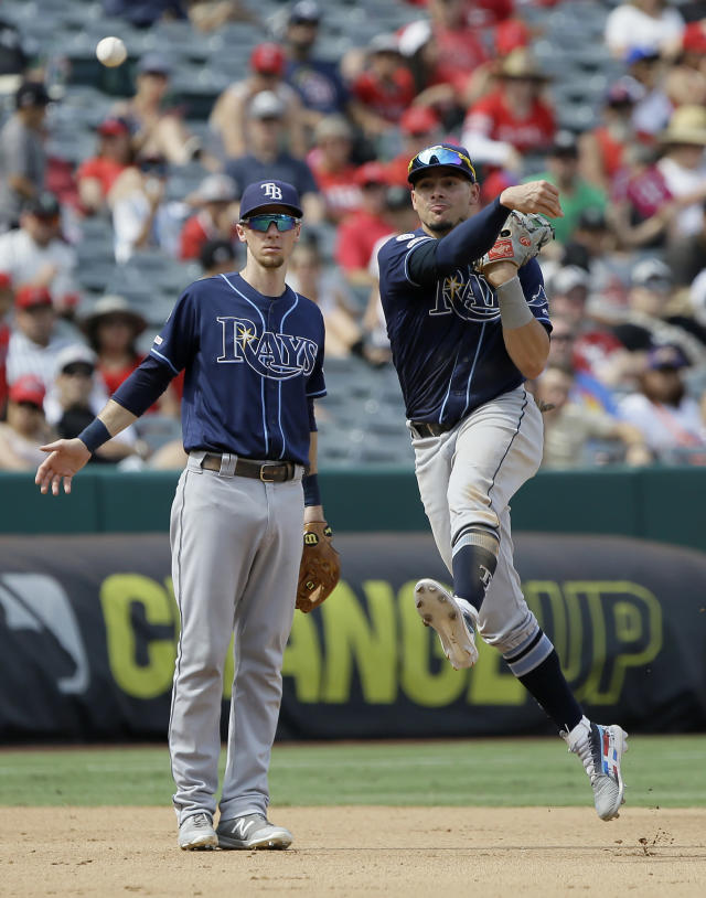 Tampa Bay Rays shortstop Willy Adames, right, throws out Los Angeles Angels' Luis Rengifo, on a ground out with third baseman Matt Duffy, left, watching during the fourth inning of a baseball game in Anaheim, Calif., Sunday, Sept. 15, 2019. (AP Photo/Alex Gallardo)