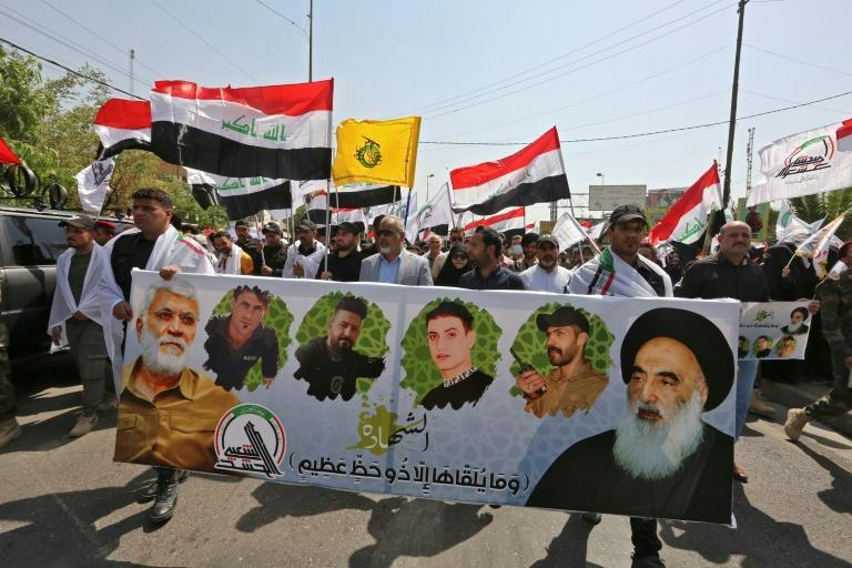 Mourners march with a banner showing (L to R) Iraq's slain Hashed al-Shaabi commander Abu Mahdi al-Muhandis, other slain members of the group and Iraq's top Shiite cleric Grand Ayatollah Ali al-Sistani, during a symbolic funeral in the Iraqi capital