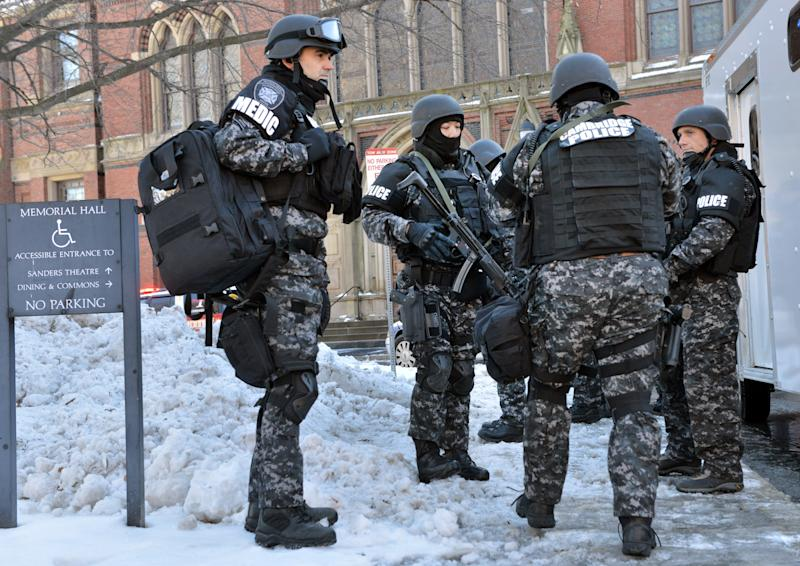 Tactical police assemble outside a building at Harvard University in Cambridge, Mass., Monday, Dec. 16, 2013. Four buildings on campus were evacuated after campus police received an unconfirmed report that explosives may have been placed inside, interrupting final exams. (AP Photo/Josh Reynolds)