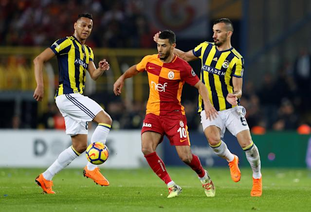 Soccer Football - Turkish Super League - Fenerbahce S.K vs Galatasaray - Sukru Saracoglu Stadium, Istanbul, Turkey - March 17, 2018 Galatasaray's Younes Belhanda in action with Fenerbahce's Souza and Mehmet Topal REUTERS/Murad Sezer