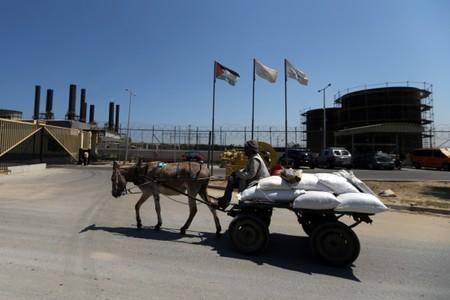 Palestinian man rides a donkey-drawn cart past the Gaza power plant, in the central Gaza Strip