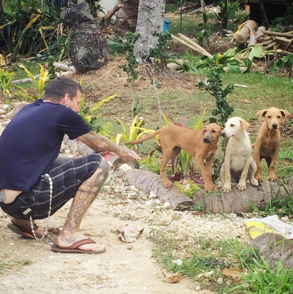 Angela's partner James shown with three stray dogs. Source: Angela Glover