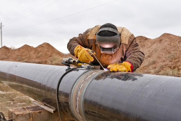 Welder working on pipeline with mounds of dirt behind.