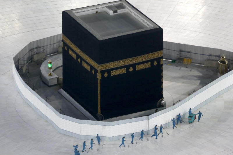 Workers disinfect the ground around the Kaaba, the cubic building at the Grand Mosque, in the Muslim holy city of Mecca, Saudi Arabia, Saturday, March 7, 2020. Saudi Arabia emptied Islam's holiest site for what they say sterilization over fears of the new coronavirus. (AP Photo/Amr Nabil)