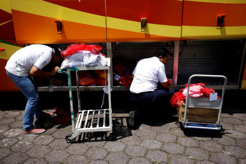 FILE PHOTO: Immigration workers process bags with belongings at an immigration facility after a flight carrying illegal immigrants from the U.S. arrived in San Salvador