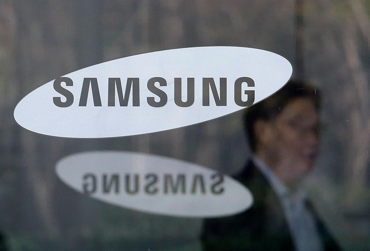 <p> FILE - In this April 6, 2018 file photo, An employee walks past logos of the Samsung Electronics Co. at its office in Seoul, South Korea. Samsung Electronics said Thursday, April 26, 2018 its first-quarter earnings jumped 52 percent over a year earlier thanks to its mainstay memory chips that posted another record-high quarterly profit. (AP Photo/Ahn Young-joon, File) </p>