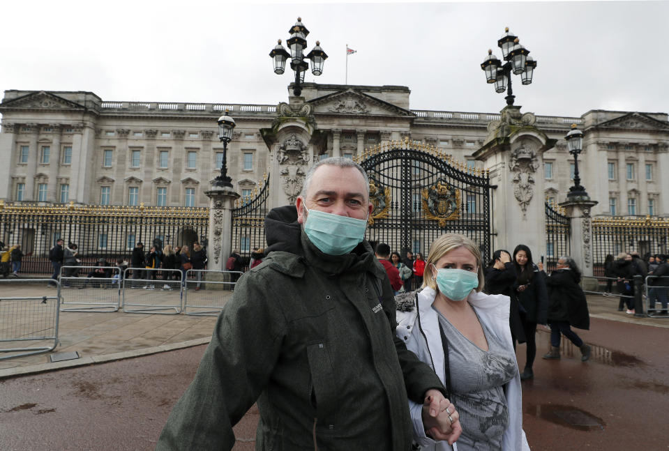 A couple wear face masks as they visit Buckingham Palace in London, Saturday, March 14, 2020. For most people, the new coronavirus causes only mild or moderate symptoms, such as fever and cough. For some, especially older adults and people with existing health problems, it can cause more severe illness, including pneumonia. (AP Photo/Frank Augstein)