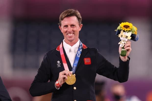 Gold medallist Ben Maher of Team Great Britain poses on the podium during the medal ceremony for the equestrian jumping individual final at Tokyo Equestrian Park in Japan on Wednesday. (Julian Finney/Getty Images - image credit)