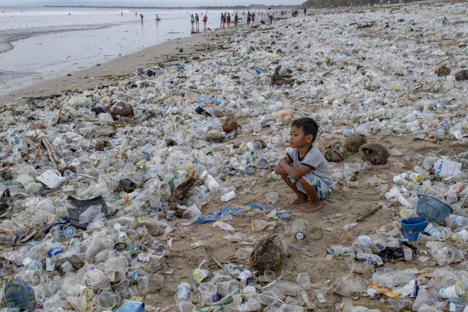 A child squats among the rubbish on an Indonesian beach.