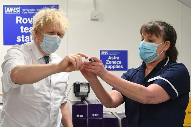 Prime Minister Boris Johnson is shown a vial of the Oxford/AstraZeneca coronavirus vaccine during a visit to Barnet FC's ground at The Hive, north London, which is being used as a coronavirus vaccination centre