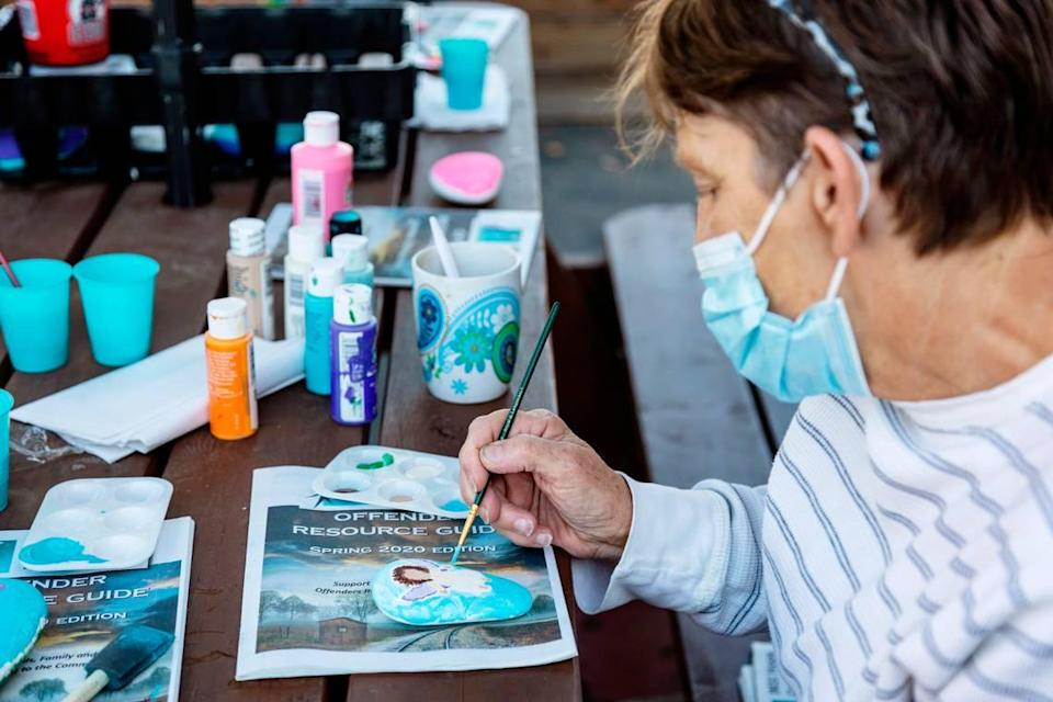 Interfaith Sanctuary resident Sherri paints an image of an angel on a rock as part of a memorial project for a fellow resident at the homeless shelter who was unvaccinated and died from COVID-19.
