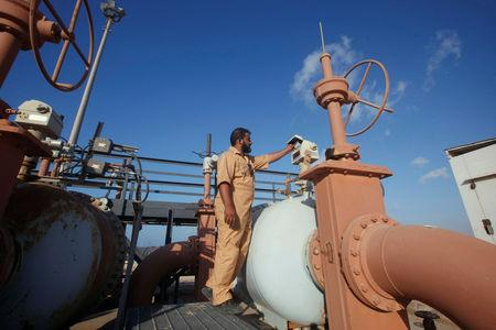 FILE PHOTO: Khalifa Mohamed Mazk inspects a pipeline at Marsa al Hariga oil port in the city of Tobruk, approximately 1,500 km (932 miles) east of Tripoli August 20, 2013. REUTERS/Ismail Zitouny/File Photo