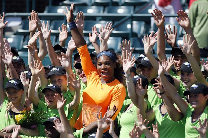 Serena Williams celebrates with the ball boys and ball girls after winning the Family Circle Cup against Jelena Jankovic, of Serbia, during the singles final at the Family Circle Cup tennis tournament in Charleston, S.C., Sunday, April 7, 2013.  Williams defeated Jankovic 3-6, 6-0, 6-2, to win the Family Circle Cup. (AP Photo/Mic Smith)