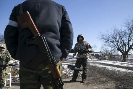 A fighter with the separatist self-proclaimed Donetsk People's Republic Army stands guard at a checkpoint along a road from the town of Vuhlehirsk to Debaltseve in Ukraine, in this picture taken February 18, 2015. REUTERS/Baz Ratner