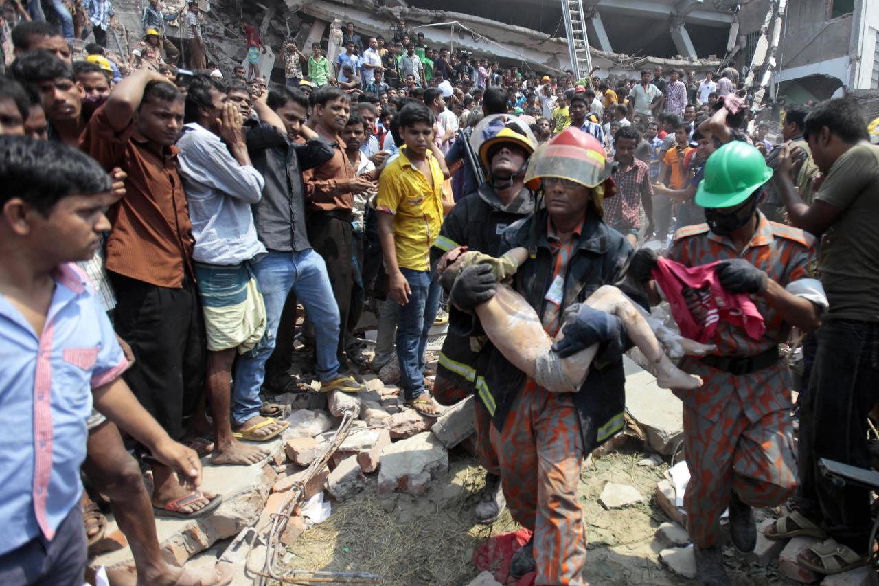 Rescue workers carry a young victim's body after an eight-story building housing several garment factories collapsed in Savar, near Dhaka, Bangladesh, Wednesday, April 24, 2013. Dozens were killed and many more are feared trapped in the rubble. (AP Photo/ A.M. Ahad)