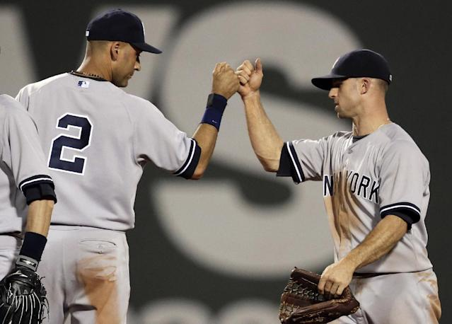 New York Yankees' Derek Jeter, left, celebrates with Brett Gardner, right, moments after the Yankees defeated the Boston Red Sox 8-7 in a baseball game, in Boston, Sunday, Aug. 3, 2014. (AP Photo/Steven Senne)
