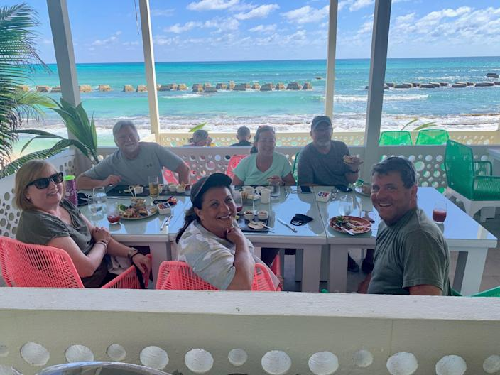 Lucia Rooney, in a light green shirt facing the camera, dines with friends and family members in Riviera Maya, Mexico.