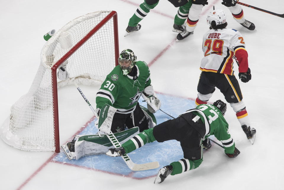 Calgary Flames' Dillon Dube (29) scores on Dallas Stars goalie Ben Bishop (30) as Stars' Esa Lindell (23) defends during the first period of an NHL hockey Stanley Cup first-round playoff series, Thursday, Aug. 13, 2020, in Edmonton, Alberta. (Jason Franson/The Canadian Press via AP)