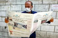 A man, clad in mask due to Covid-19 coronavirus pandemic, reads a copy of the Kayhan newspaper, considered to be the mouthpiece of ultraconservatives in Iran, in August 2020