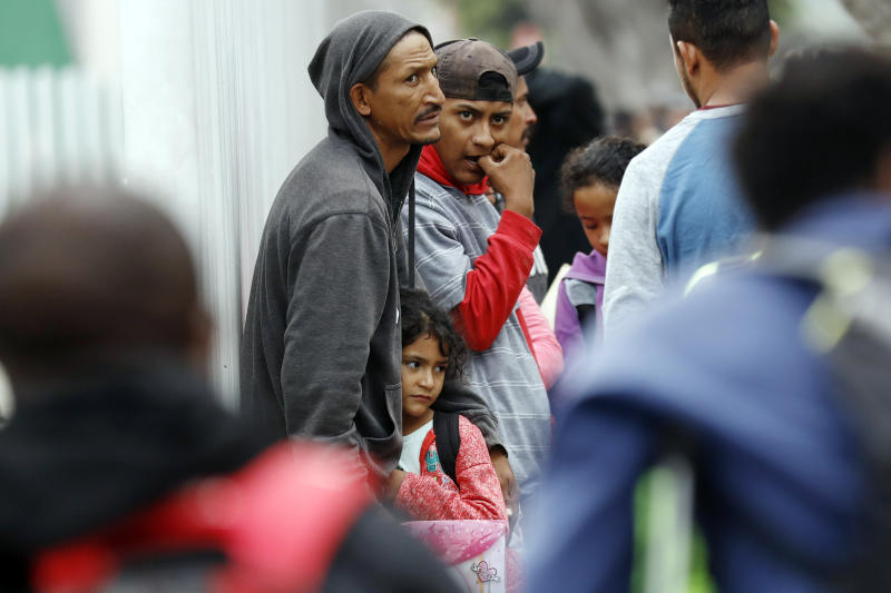 FILE - In this July 16, 2019 file photo, people wait to apply for asylum in the United States along the border in Tijuana, Mexico. The American Civil Liberties Union said Tuesday, July 30, 2019 that more than 900 children have been separated from their families at the border since a judge ordered last year that the practice be sharply curtailed. The ACLU says about one of every five children separated is under 5 years old. (AP Photo/Gregory Bull, File)