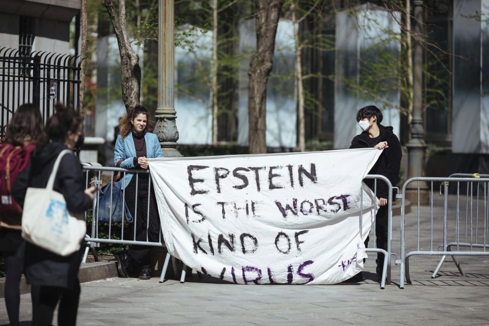 Activists protesting Jeffrey Epstein's associate Ghislaine Maxwell stand in front of Federal Court on Friday, April 23, 2021, in New York. Ghislaine Maxwell, a British socialite and one-time girlfriend of Epstein, pleaded not guilty to sex trafficking conspiracy and an additional sex trafficking charge that were added in a rewritten indictment released last month by a Manhattan federal court grand jury. (AP Photo/Kevin Hagen)