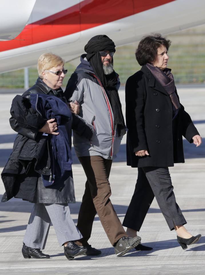 Former French hostage Marc Feret (C) is welcomed by relatives on the tarmac upon his arrival at Villacoublay military airport, near Paris, October 30, 2013. Four Frenchmen Pierre Legrand, Daniel Larribe, Thierry Dol and Marc Feret held hostage in the Sahara desert by al Qaeda-linked gunmen for three years left Niger on a French government plane on Wednesday morning. The men, who were kidnapped in 2010 while working for French nuclear group Areva and a subsidiary of construction group Vinci in northern Niger, were freed on Tuesday after secret talks. REUTERS/Philippe Wojazer (FRANCE - Tags: POLITICS)