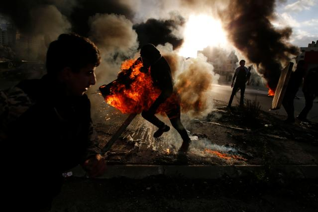 <p>A Palestinian protester runs after catching fire during clashes with Israeli troops at a protest against President Donald Trump's decision to recognize Jerusalem as the capital of Israel, near the Jewish settlement of Beit El, near the West Bank city of Ramallah on Dec. 7, 2017. (Photo: Abbas Momani/AFP/Getty images) </p>