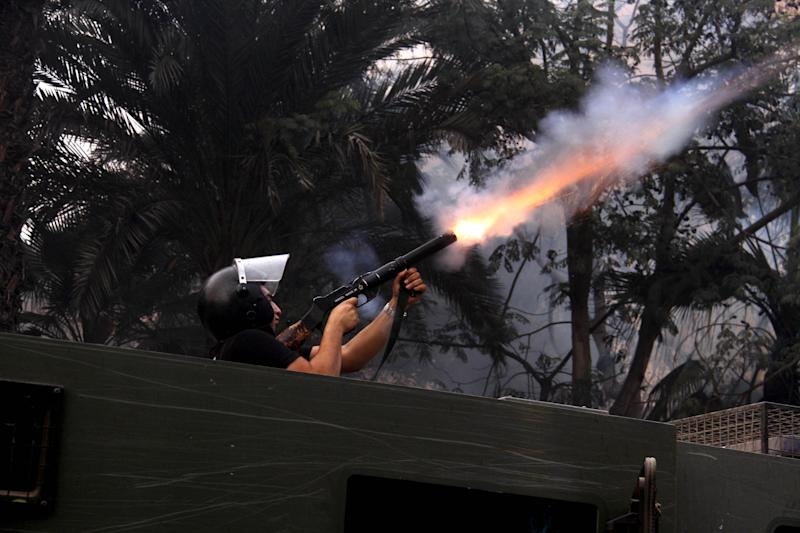An Egyptian riot policeman fires tear gas in Cairo, Egypt, Friday, Nov. 29, 2013, to disperse hundreds of Islamist demonstrators defying a new protest law that has drawn widespread criticism from the international community and democracy advocates.(AP Photo/Ahmed Gomaa)