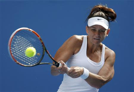 Casey Dellacqua of Australia hits a return to Kirsten Flipkens of Belgium during their women's singles match at the Australian Open 2014 tennis tournament in Melbourne January 15, 2014. REUTERS/Bobby Yip
