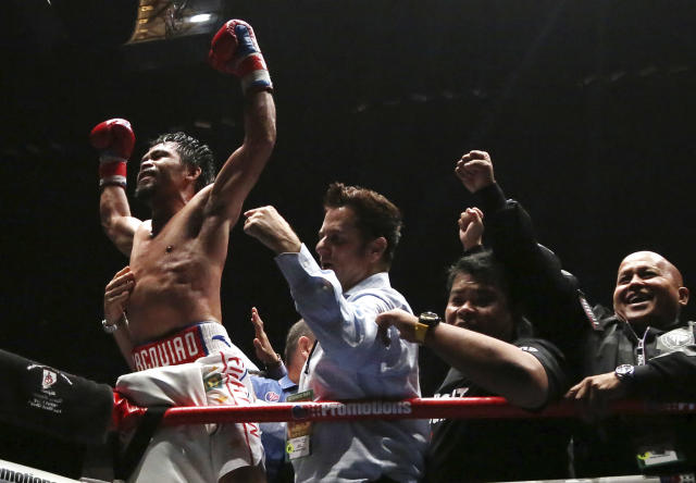 Manny Pacquiao of the Philippines, left, celebrates after defeating Lucas Matthysse of Argentina during their WBA World welterweight title bout in Kuala Lumpur, Malaysia, Sunday, July 15, 2018. Filipino boxing legend Pacquiao clinched his 60th victory Sunday with a seventh-round knockout of Matthysse, his first stoppage in nine years, that will help revive his career.(AP Photo/Yam G-Jun)