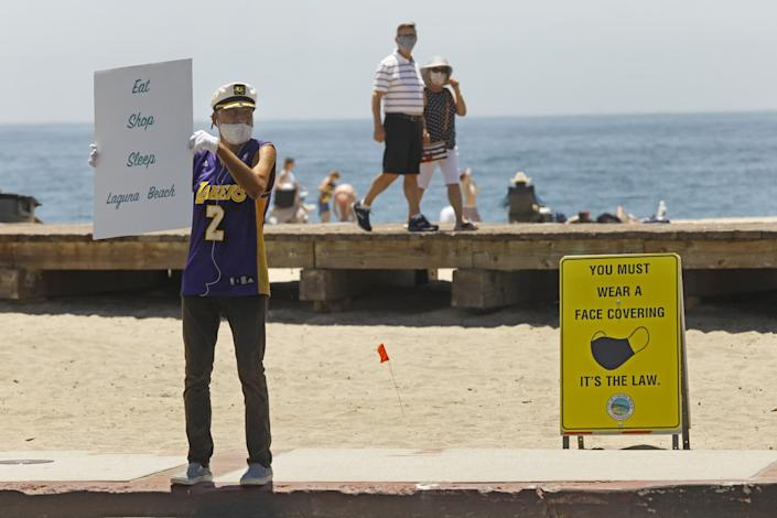 "Laguna Beach self-appointed greeter, Michael Minutoli wears a mask while promoting the town. <span class=""copyright"">(Carolyn Cole/Los Angeles Times)</span>"