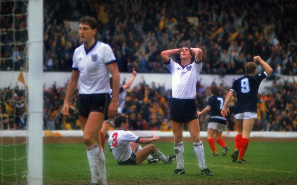 A dejected Terry Fenwick (centre), Terry Butcher (left) and Kenny Sansom (#3 on the ground, who had been beaten for the header) react after Richard Gough's winning goal for Scotland, at Hampden - Colorsport/Shutterstock