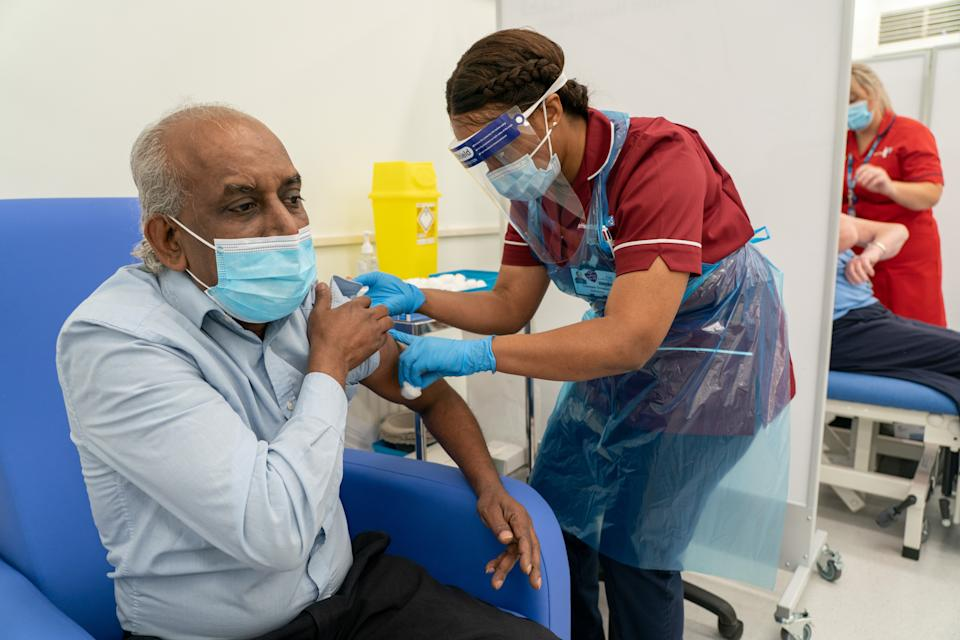 Care home worker Pillay Jagambrun, 61, receives the Pfizer-BioNTech Covid-19 vaccine in The Vaccination Hub at Croydon University Hospital, south London, on the first day of the largest immunisation programme in the UK's history. Care home workers, NHS staff and people aged 80 and over began receiving the jab this morning.