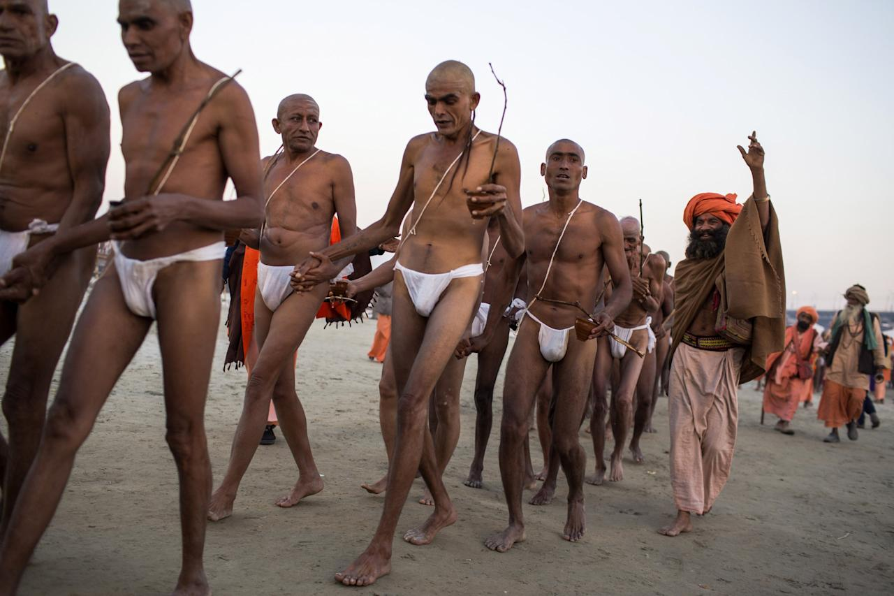 ALLAHABAD, INDIA - FEBRUARY 08: Naga sadhus, naked Hindu holy men, participate in an initiation ceremony on the banks of the Ganges river during the Maha Kumbh Mela on February 8, 2013 in Allahabad, India. The Maha Kumbh Mela, believed to be the largest religious gathering on earth is held every 12 years on the banks of Sangam, the confluence of the holy rivers Ganga, Yamuna and the mythical Saraswati. The Kumbh Mela alternates between the cities of Nasik, Allahabad, Ujjain and Haridwar every three years. The Maha Kumbh Mela celebrated at Sangam, is the largest and holiest, celebrated over 55 days, it is expected to attract over 100 million pilgrims who will bathe in holy waters to wash away their sins. (Photo by Daniel Berehulak/Getty Images)