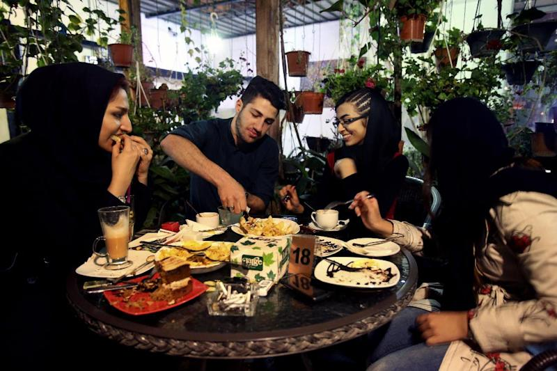 """In this Tuesday, March 4, 2014 photo, young Iranian adults eat at a cafe in Tehran, Iran. For years Iranian authorities kept the number of cafes limited since they were seen as a symbol of Western influence and places to spread non-Islamic beliefs. But reports of cafes being shut because they violate """"Islamic dignities"""" have dropped markedly in recent months, suggesting a growing tolerance by the authorities. (AP Photo/Vahid Salemi)"""
