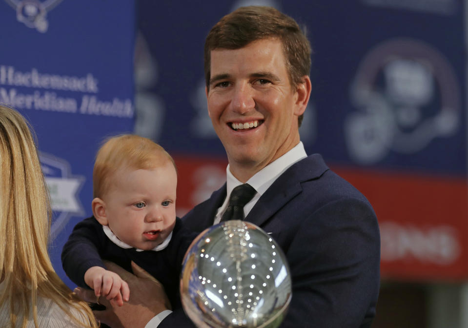 New York Giants NFL football quarterback Eli Manning holds his son Charles after announcing his retirement on Friday, Jan. 24, 2020, in East Rutherford, N.J. (AP Photo/Adam Hunger)