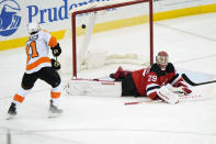 Philadelphia Flyers center Scott Laughton (21) scores as he flips the puck behind New Jersey Devils goaltender Mackenzie Blackwood (29) during the second period of an NHL hockey game Thursday, April 29, 2021, in Newark, N.J. (AP Photo/Kathy Willens)
