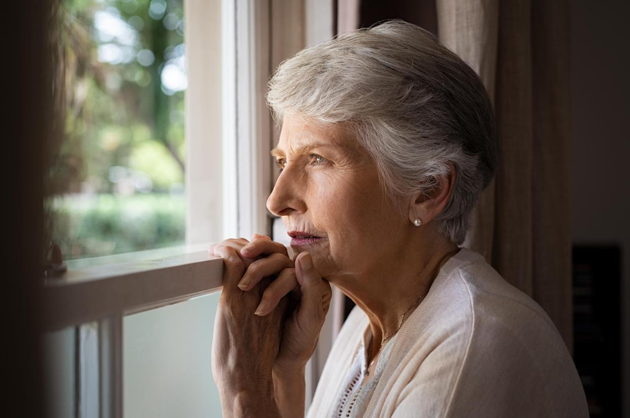 Depressed senior woman at home feeling sad. Elderly woman looks sadly outside the window. Depressed lonely lady standing alone and looking through the window.