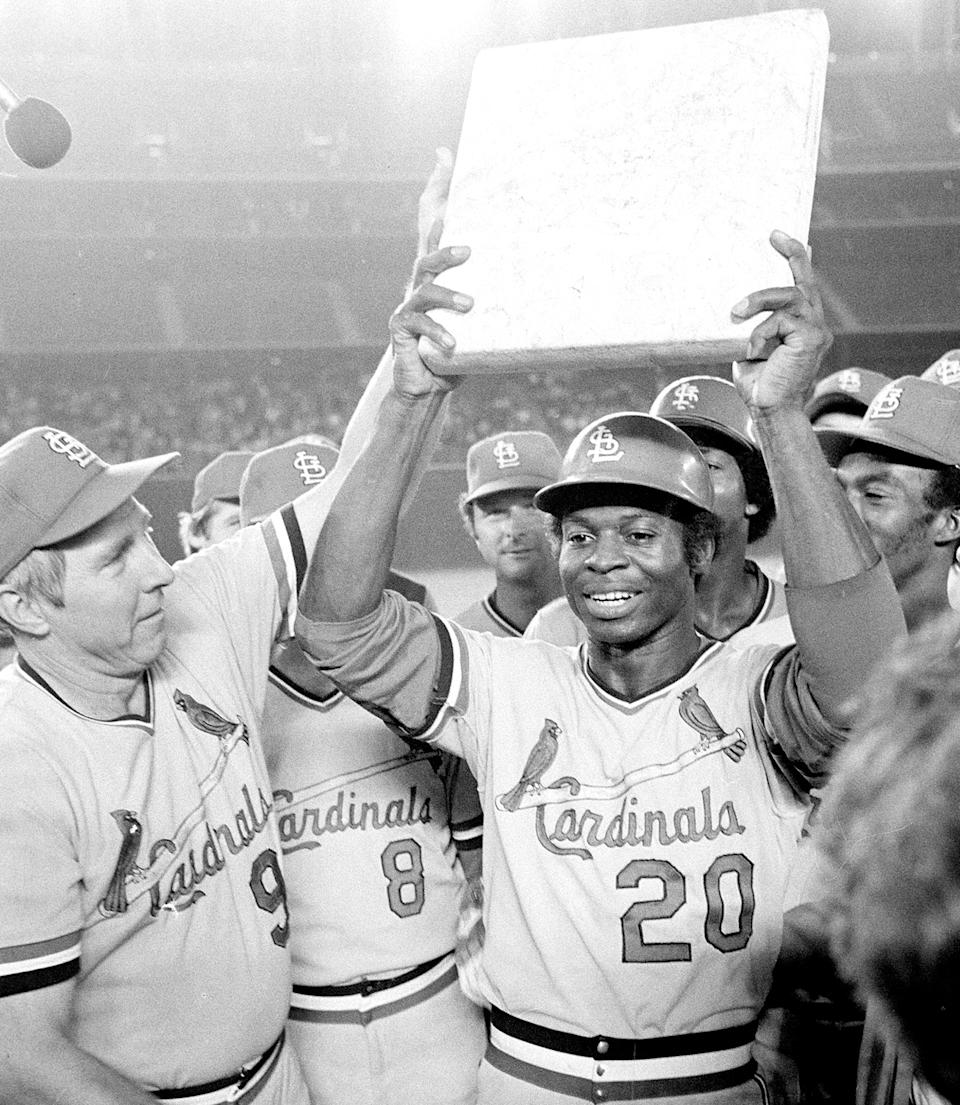 FILE - St. Louis Cardinals shortstop Lou Brock is surrounded by teammates as he holds second base after breaking Ty Cobb's all-time record of 892 stolen bases during a game against the San Diego Padres in San Diego, Calif., in this Monday night, Aug. 29, 1977, file photo. At left is team manager Vern Rapp. The list is disquieting in its length - those from the ranks of 1970s baseball rosters who have died in the past year alone. (AP Photo/File)