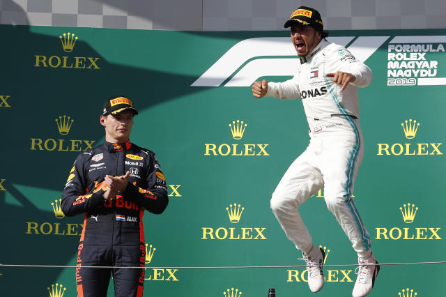 Mercedes driver Lewis Hamilton, right, of Britain celebrates on the podium with second placed Red Bull driver Max Verstappen, of the Netherlands, after winning the Hungarian Formula One Grand Prix at the Hungaroring racetrack in Mogyorod, northeast of Budapest, Hungary, Sunday, Aug. 4, 2019. (AP Photo/Laszlo Balogh)