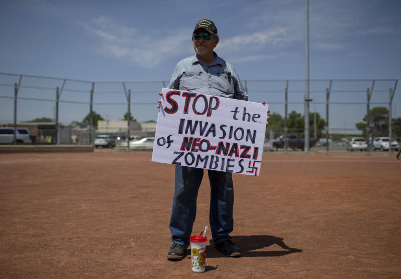 Gilberto Zuniga holds a sign to protest the visit of President Donald Trump to the border city after the Aug. 3 mass shooting in El Paso, Texas, Wednesday, Aug. 7, 2019.  Trump headed to El Paso, after visiting  Dayton, Ohio on Wednesday to offer a message of healing and unity, but he will be met by unusual hostility in both places by people who fault his own incendiary words as a contributing cause to the mass shootings.  (AP Photo/Andres Leighton)
