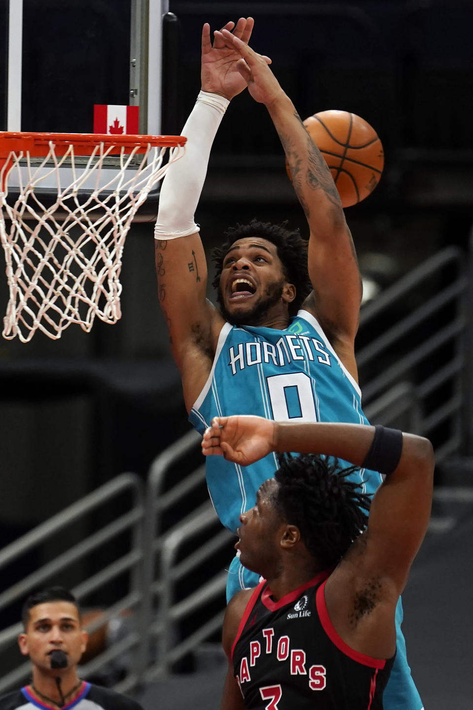 Charlotte Hornets forward Miles Bridges (0) can't handle a pass after getting past Toronto Raptors forward OG Anunoby (3) during the second half of an NBA basketball game Saturday, Jan. 16, 2021, in Tampa, Fla. (AP Photo/Chris O'Meara)