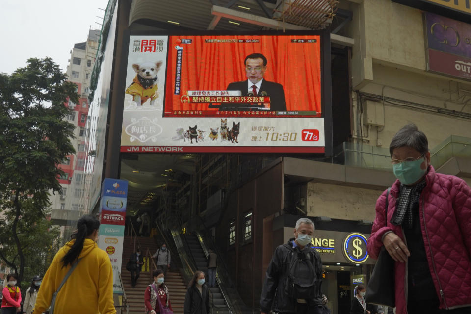 A TV screen broadcasts the news of the opening session of China's National People's Congress (NPC), in Hong Kong, Friday, March 5, 2021. A senior Chinese official says the largely pro-Beijing committee that currently elects the Hong Kong's leader will also elect some members of the city's legislature, as part of Beijing's planned revamp of Hong Kong's electoral system. (AP Photo/Kin Cheung)