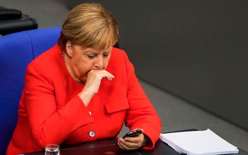 'When a phone rings, do you react as if a gun has gone off?' - Angela Merkel stares at her smartphone during a sitting of the Bundestag - AFP