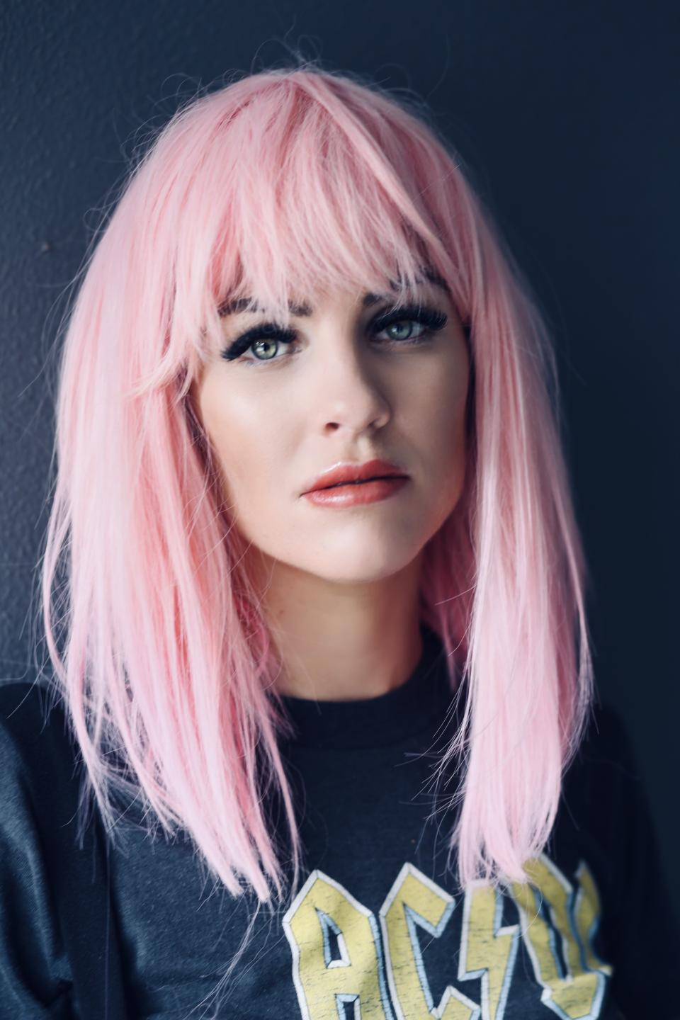 Booka Nile wearing a pink wig, an AC/DC t-shirt and black short dungarees