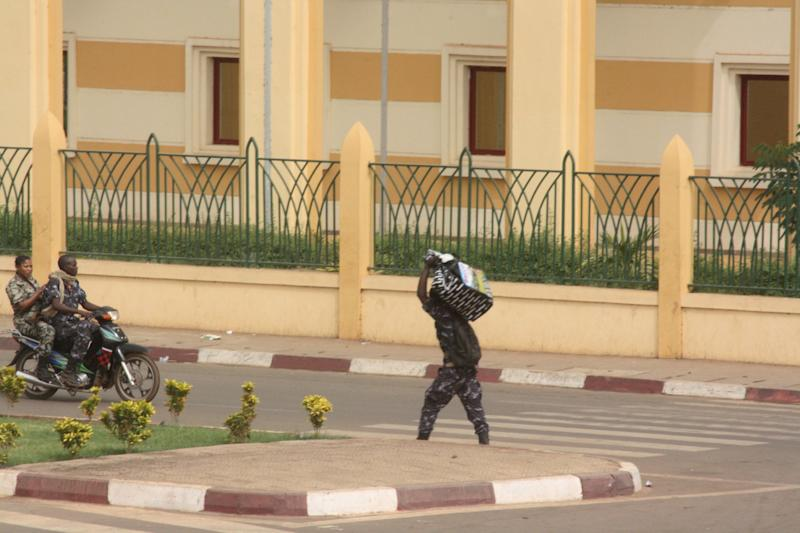 A soldier carries goods away from a compound housing various government ministries a day after a military coup, in Bamako, Mali, Thursday March 22, 2012. Soldiers are reported to have looted Mali's presidential palace hours after they declared a coup on Thursday, suspending the constitution and dissolving the institutions of one of the few established democracies in this troubled corner of Africa. The whereabouts of the country's 63-year-old president Amadou Toumani Toure, who was just one month away from stepping down after a decade in office, could not be confirmed. (AP Photo/Harouna Traore)