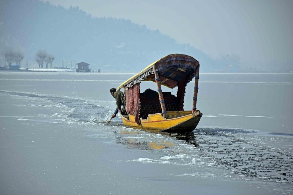 A local shikarawala trying to break the sheet of ice covering the Dal Lake in order to row across the lake.